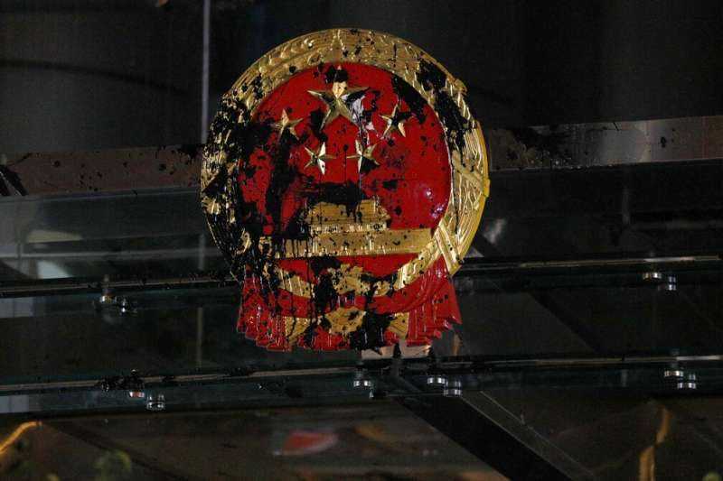 中聯辦外的香港國徽遭到黑色油漆彈擊中。(美聯社)