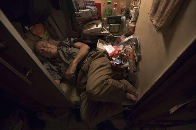 超過20萬香港人住在非法劏房裡,80歲的張先生睡在劏房裡,甚至無法將腳伸直(美聯社)