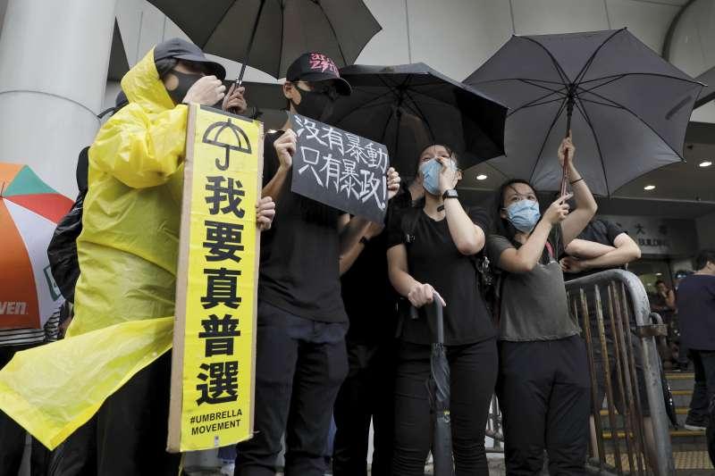 香港民眾手持「我要真普選」標語,冒雨聲援7月28日上環衝突中被控「暴動罪」的44人。(AP)