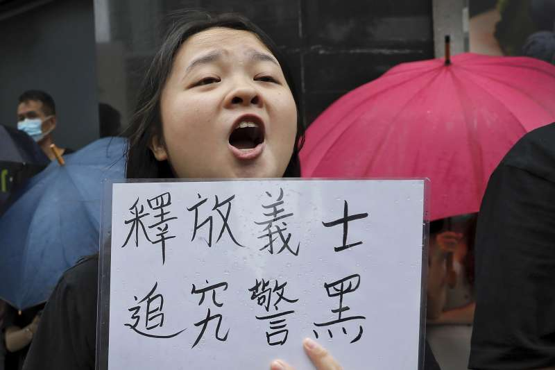香港民眾手持「釋放義士、追究警黑」標語,聲援7月28日上環衝突中被控「暴動罪」的44人。(AP)