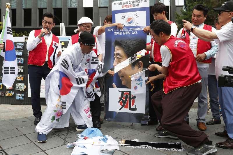 日韓貿易戰越演越烈,南韓民眾破壞印有日相安倍晉三的海報。(AP)