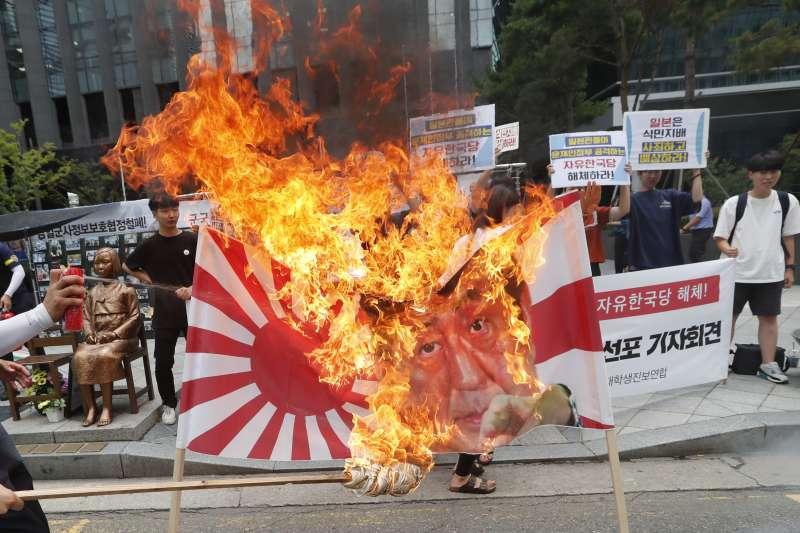 日韓貿易戰越演越烈,南韓民眾焚燒日本太陽旗。(AP)