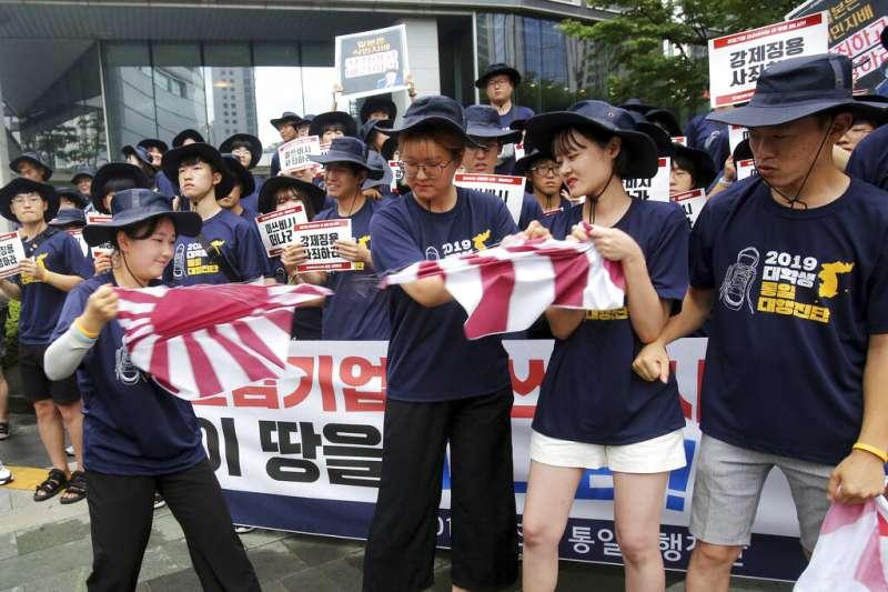 南韓民眾在首爾的三菱分公司外抗議,撕毀日本的太陽旗。(美聯社)
