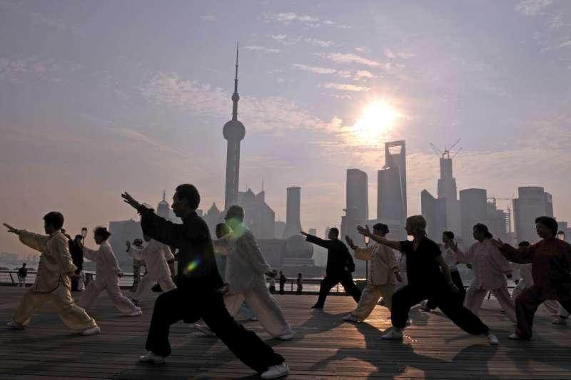 2012年10月3日清晨,上海市黃浦區外灘紀念塔太極拳輔導站的太極愛好者與遊客,在上海外灘陳毅廣場練習太極拳,強身健體,享受長假。(新華社)