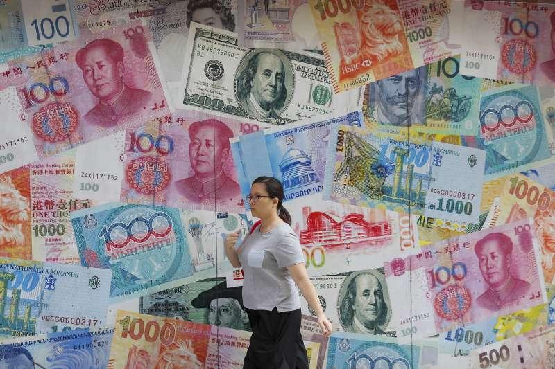 8月6日,一名女子經過香港中環一間換匯所(美聯社)