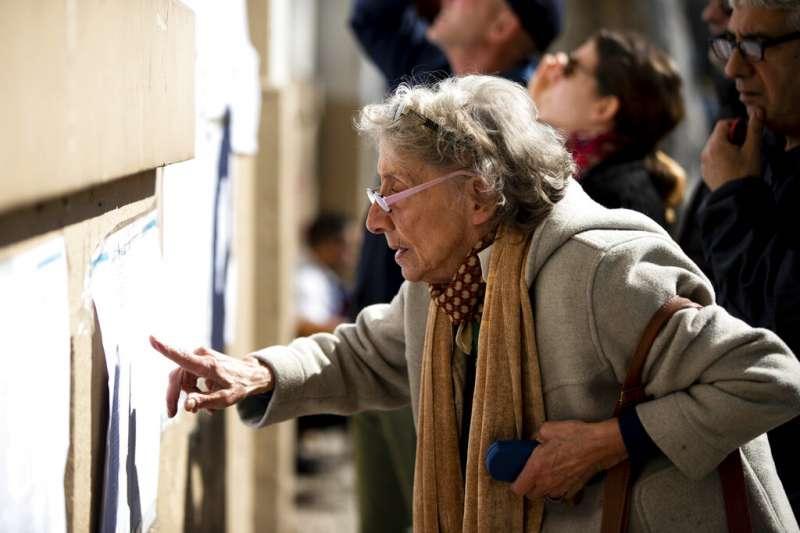 阿根廷11日舉行總統初選,一位老太太聚精會神地看著選舉公報。(美聯社)