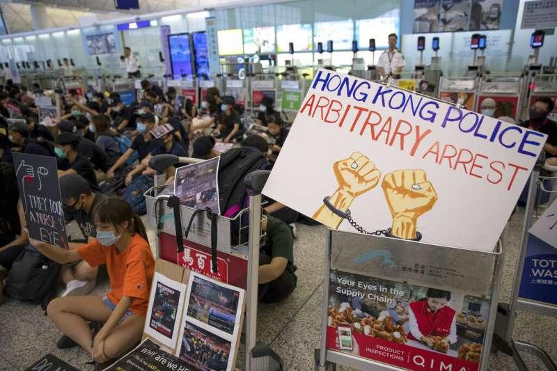 抗議「反送中」與「爆眼少女」的群眾連續第二天現身香港國際機場,癱瘓離境大廳。(美聯社)