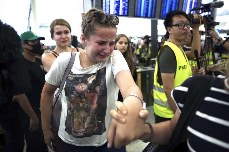 抗議「反送中」與「爆眼少女」的群眾連續第二天現身香港國際機場,無法離境的旅客試圖說服示威者讓他們通過離境大廳。(美聯社)