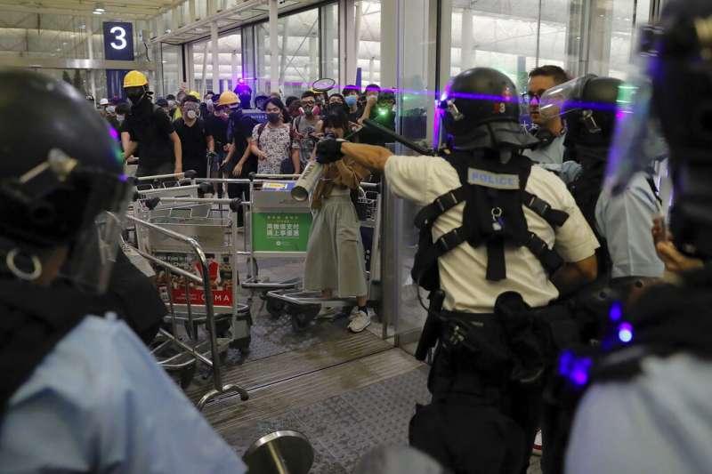 抗議「反送中」與「爆眼少女」的群眾連續第二天現身香港國際機場,癱瘓離境大廳與機場運作。(美聯社)