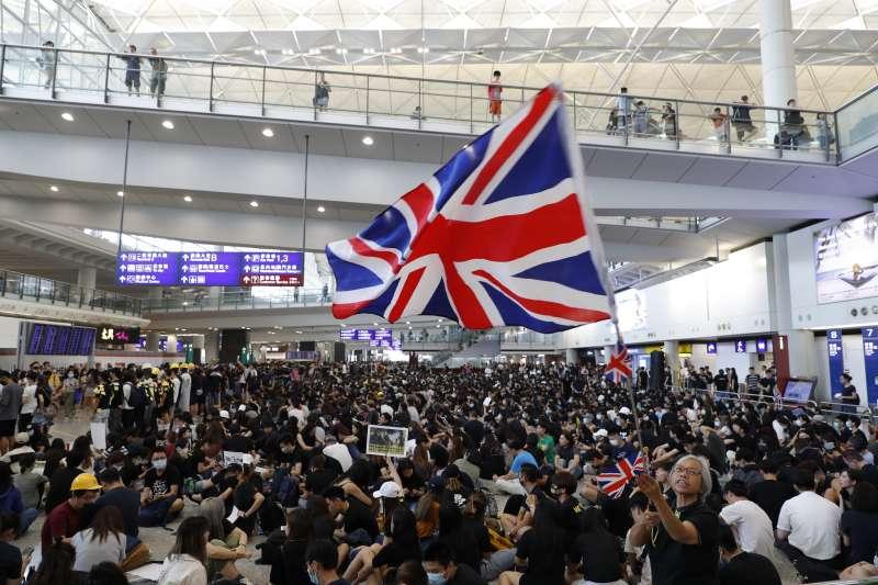 當前香港局勢,不確保兩制可能就沒有一國;不給自治更大空間,就要逼人民主張自決。中國的政治思維與體系是否運用「一國」與「兩制」的槓桿,處理當前的香港抗爭,很快就要答案揭曉。 圖為香港反送中示威者在香港國際機場高舉英國國旗。(AP)
