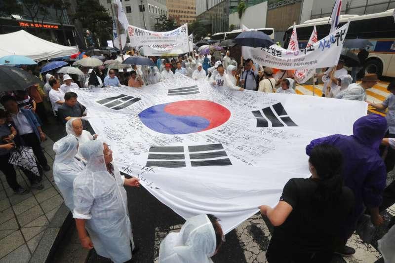 南韓的二戰受害者家屬15日拿著南韓國旗上街示威,大喊反日標語。(美聯社)