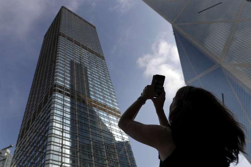 香港返送中讓蔡英不斷搶到槍。圖為「法國蜘蛛人羅伯特(Alain Robert)爬上香港一座摩天大樓,掛上旗幟呼籲和平。(AP)