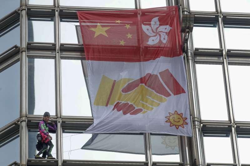2019年8月16日,「法國蜘蛛人羅伯特(Alain Robert)爬上香港一座摩天大樓,掛上旗幟呼籲和平。(AP)