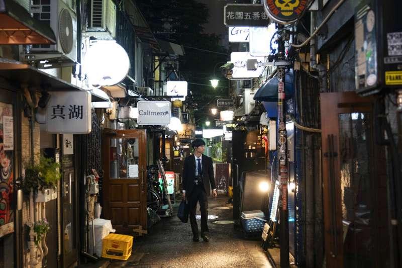 一名日本上班族在東京新宿的巷弄間遊蕩。(美聯社)