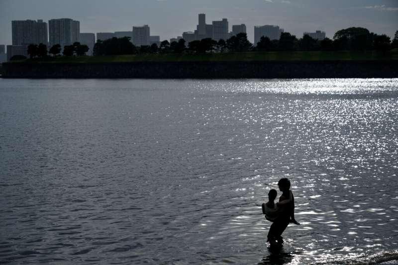 一對情侶在日本東京御台場戲水。(美聯社)