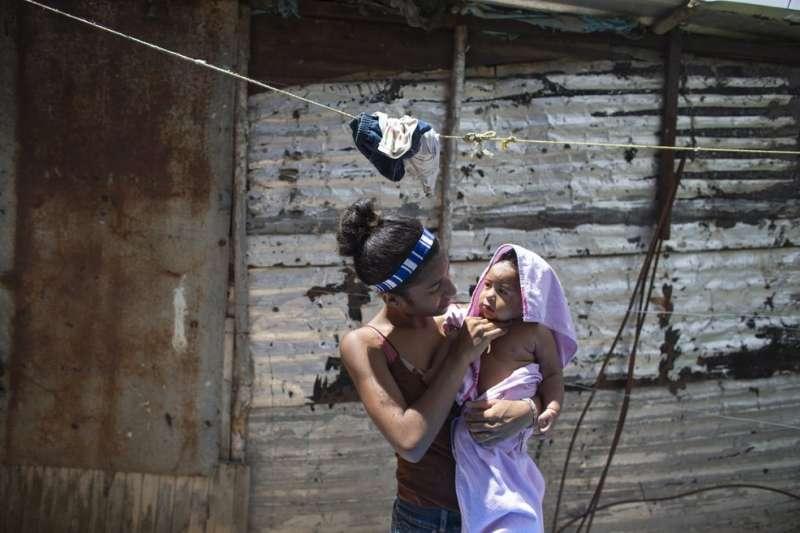 15歲的委內瑞拉小媽媽赫蕾拉抱著孩子,她說自己14歲得知懷孕時,曾經試圖自殺。(AP)