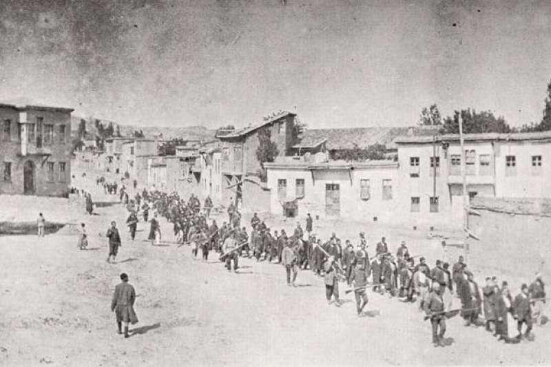 1915年4月,亞美尼亞平民在鄂圖曼士兵引領下穿過哈爾普特前往附近監獄。(取自維基百科共享資源)