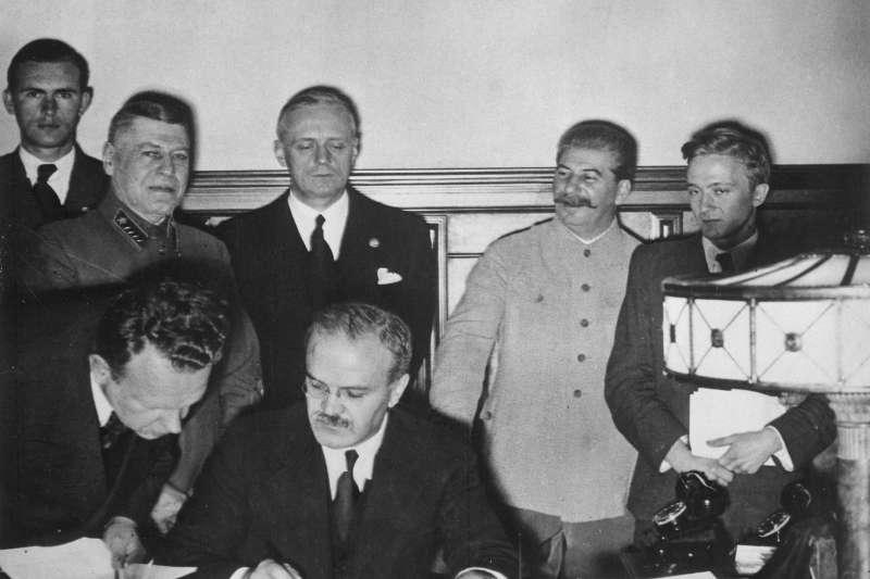 德國和蘇聯外長在1939年8月23日在莫斯科簽定《蘇德互不侵犯條約》,蘇共總書記史達林站在後面見證條約簽署。(維基百科.公有領域)