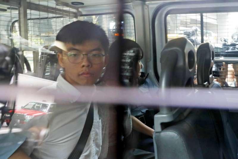 由警車押解出庭的黃之鋒與周庭。(美聯社)
