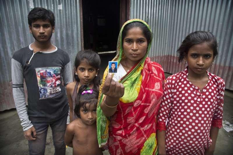 32歲的妮莎(Halimun Nessa)展示亡夫阿里(Rahim Ali)的照片。阿里擔心孩子失去公民身分,於是選擇自殺(美聯社)