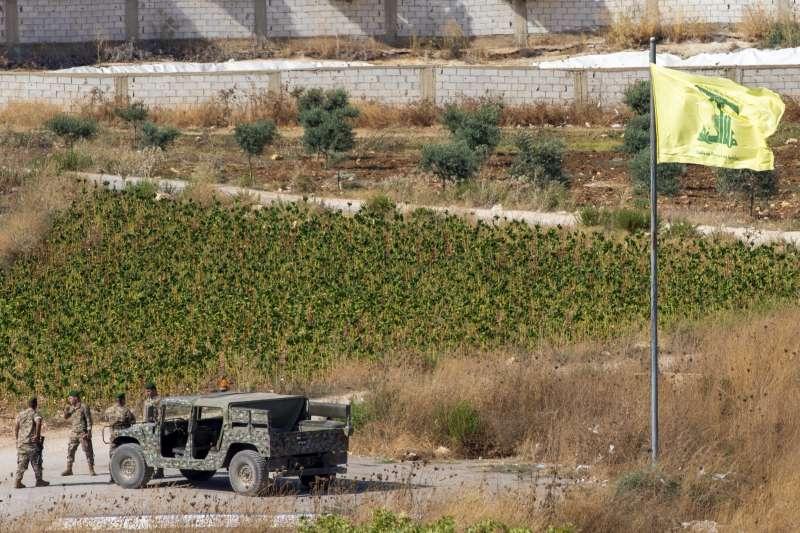以色列與黎巴嫩真主黨交火,圖為真主黨旗幟旁的黎巴嫩軍人(AP)