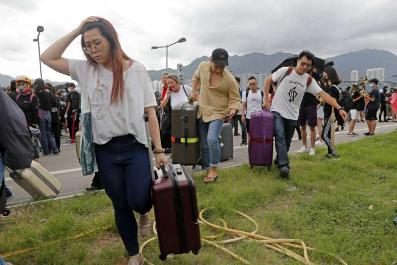 香港機場交通1日遭到抗爭者癱瘓,旅客只能拉著行李箱步行進入機場。(美聯社)
