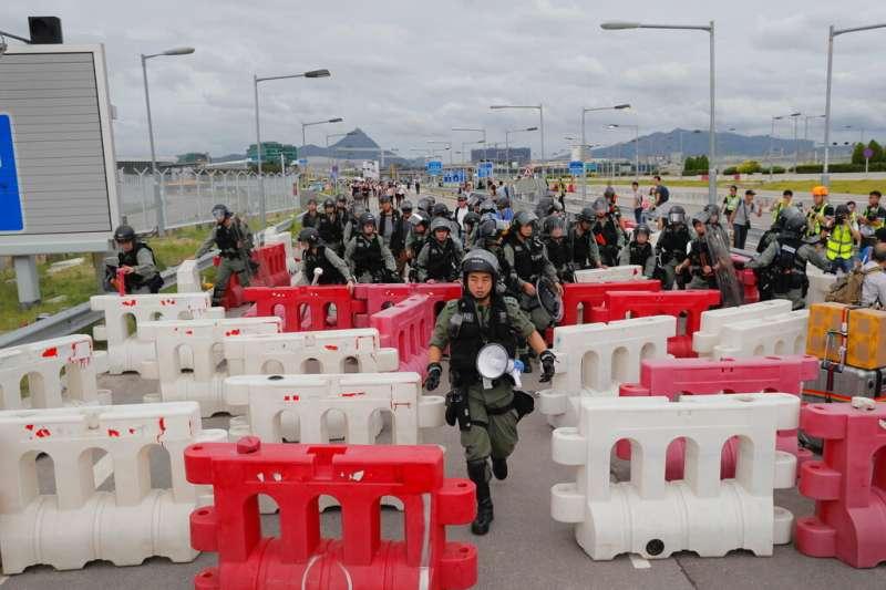 「反送中」的抗爭者1日在香港機場一帶聚集,試圖癱瘓機場對外交通,香港警察也進駐機場準備驅離抗爭者。(美聯社)