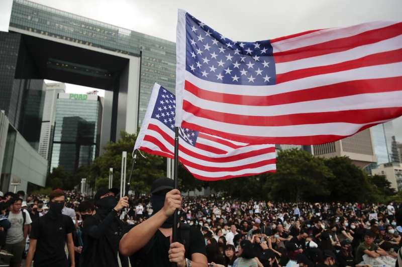 香港「反送中」群眾在政府總部外聚集,還有人高舉美國國旗。(美聯社)