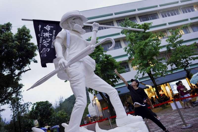 香港中文大學架設的「自由女神像」,頭盔、口罩、眼罩、防毒面具跟雨傘的裝扮,完全就是「反送中」示威者的標準裝備。(美聯社)