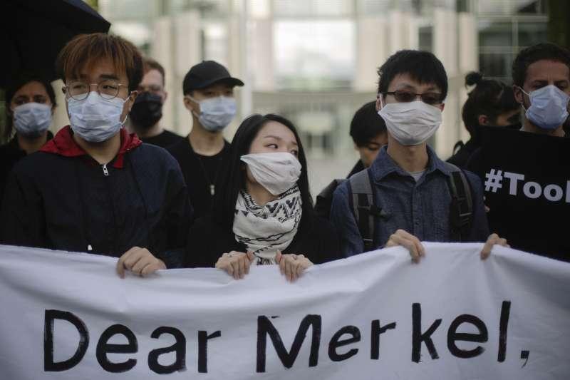 港籍/華裔民眾在柏林呼籲德國關注香港反送中與人權問題,擺出「警察還眼」手勢。(AP)
