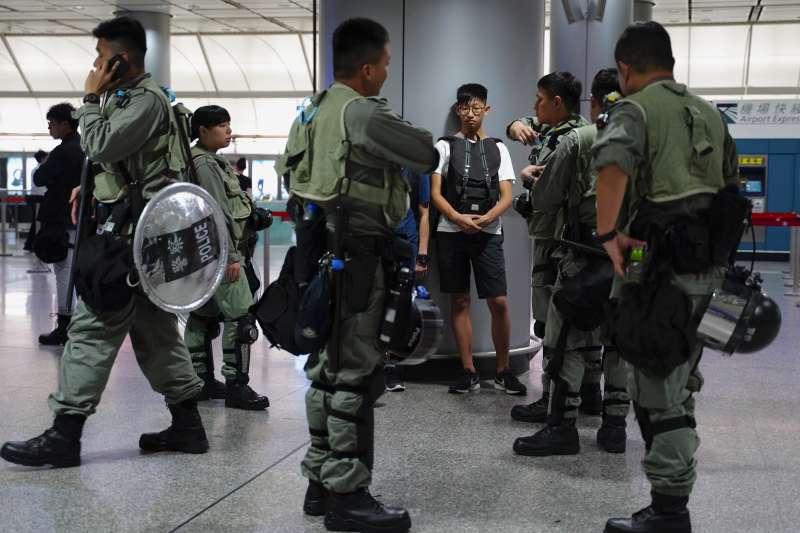 2019年8月7日,香港示威者再度發起「機場交通壓力測試」,圖為港警盤查民眾攜帶物品。(AP)