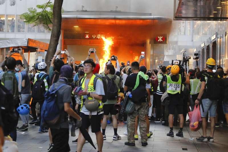 反送中示威者8日在中環地鐵站外放火。(美聯社)