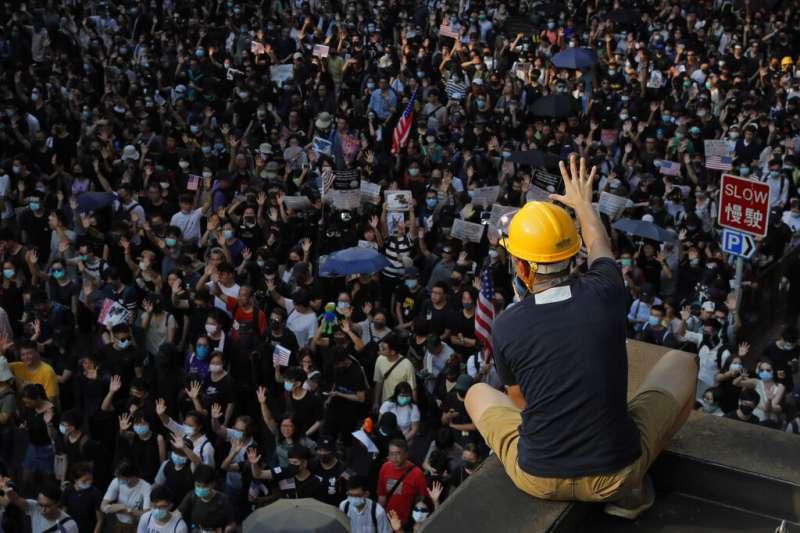 大批反送中示威者8日前往美國駐港領事館要求協助,一名抗議者在高處對群眾比出「五」的手勢,意味著「五大訴求、缺一不可」。(美聯社)