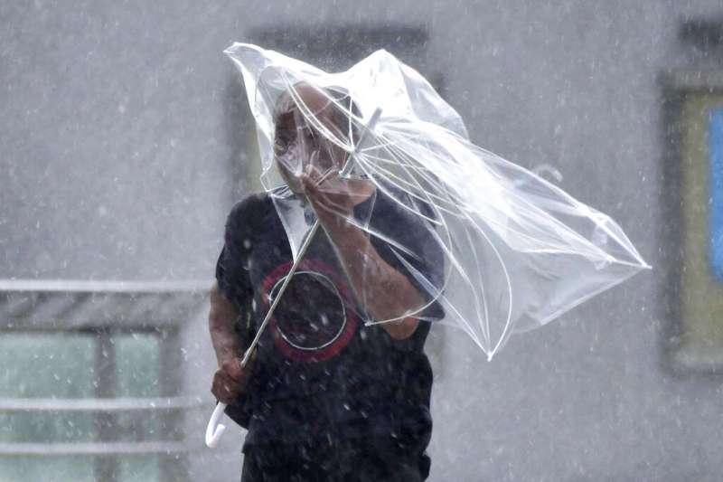 法西颱風直撲日本,磐城市一名男性撐著傘在風雨中前進。(美聯社)
