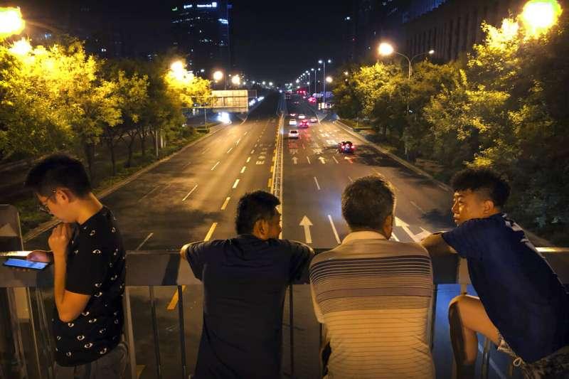 北京民眾7日深夜在天橋上等到閱兵預演。(美聯社)
