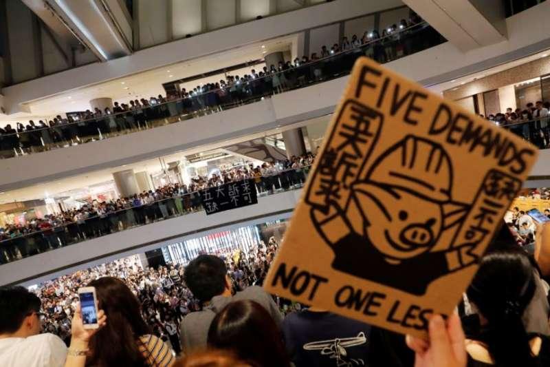 """香港抗議者在中環國際金融中心手舉""""五項訴求,缺一不可""""的標語牌大合唱《願榮光歸香港》。(美國之音)"""
