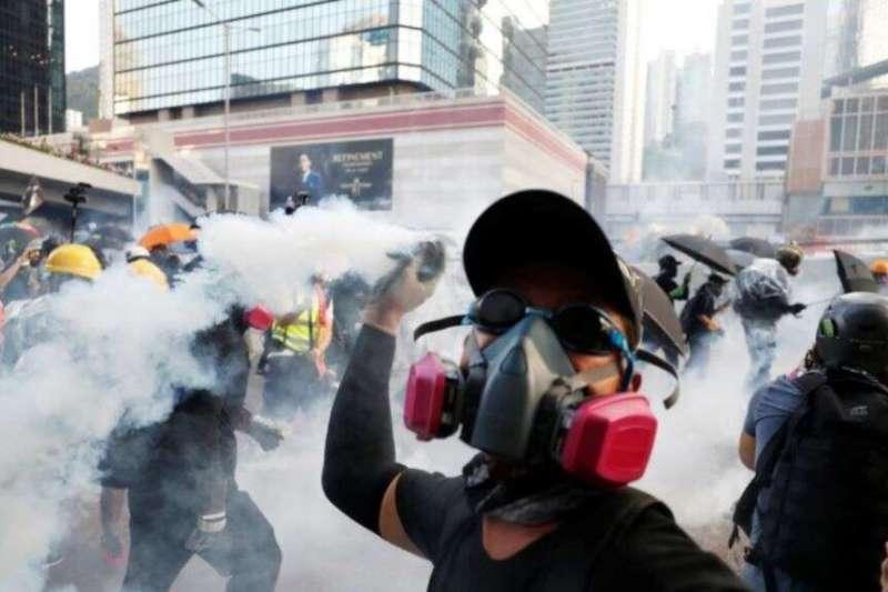 一名香港抗議者星期天(2019年9月15日)向警方扔回一枚催淚彈。(美國之音)