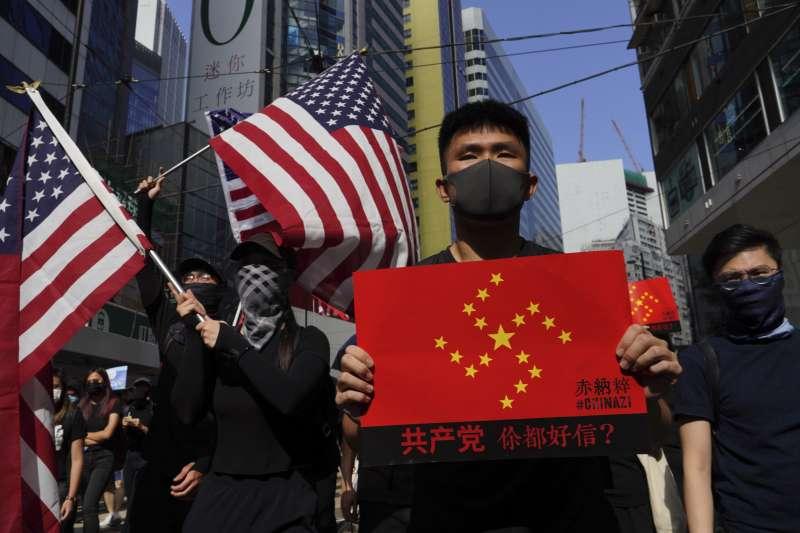 香港抗議者舉著美國國旗,把希望寄於美國政府和川普。(資料照,AP)