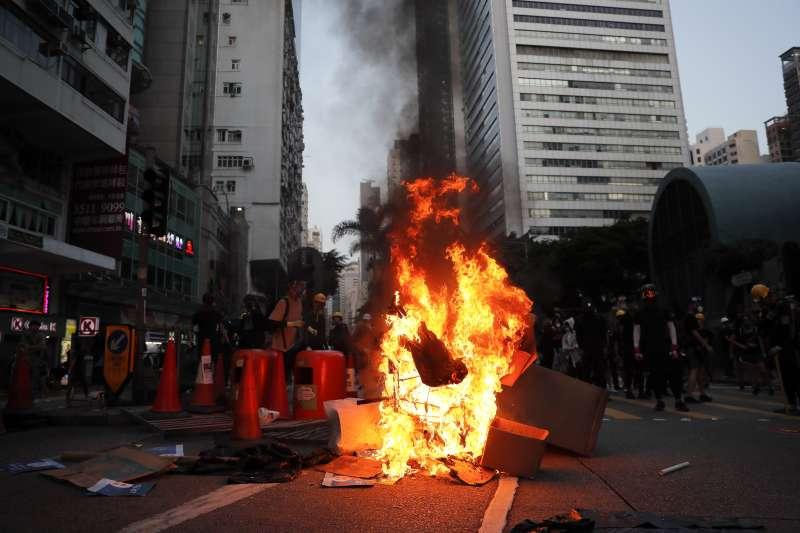 香港反送中抗爭出現焚燒五星旗、汙損中聯辦國徽的舉動,挑動著北京的神經。(AP)