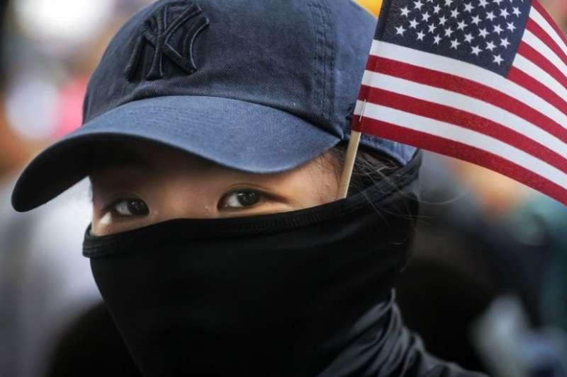 帶著美國國旗遊行的香港蒙面示威者。(BBC中文網)