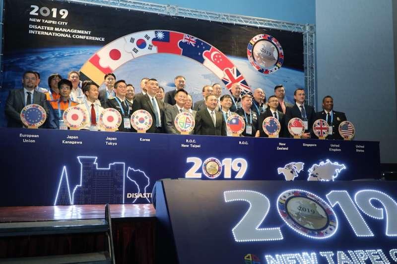 新北市長侯友宜主持「新北市2019災害管理國際研討會」開幕式,與出席貴賓合影。(圖/新北市消防局提供)