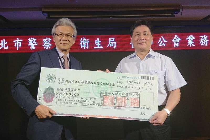 新北市醫師公會理事長周慶明(左)代表捐贈新台幣50萬元給新北市警察局推動警政,由警察局長陳檡文代表接受。(圖/新北市警察局提供)