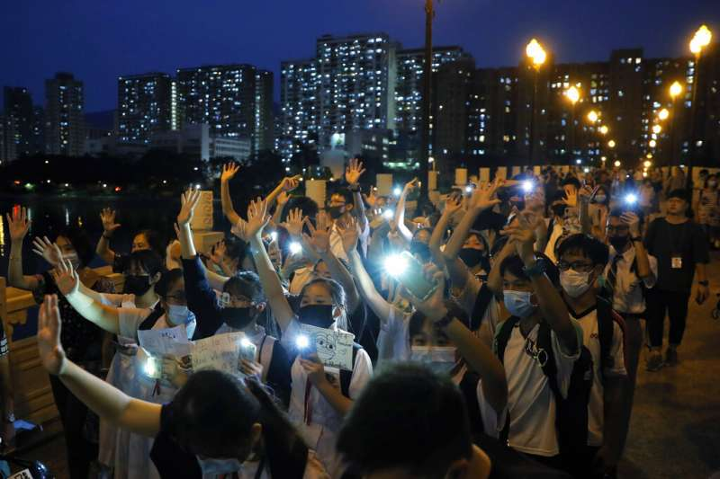 參與「反送中」抗爭的香港中學生越來越多,19日在沙田區就有許多中學生戴著口罩牽手示威,並且比出手勢堅持「五大訴求」。(美聯社)