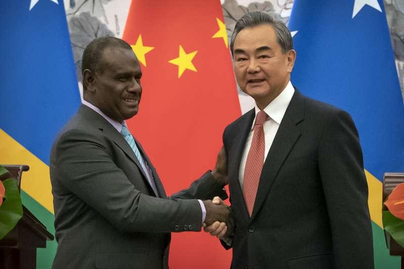 索羅門群島外交部長馬內列(左)與中國外交部長王毅(右)在北京簽署建交公報。(AP)