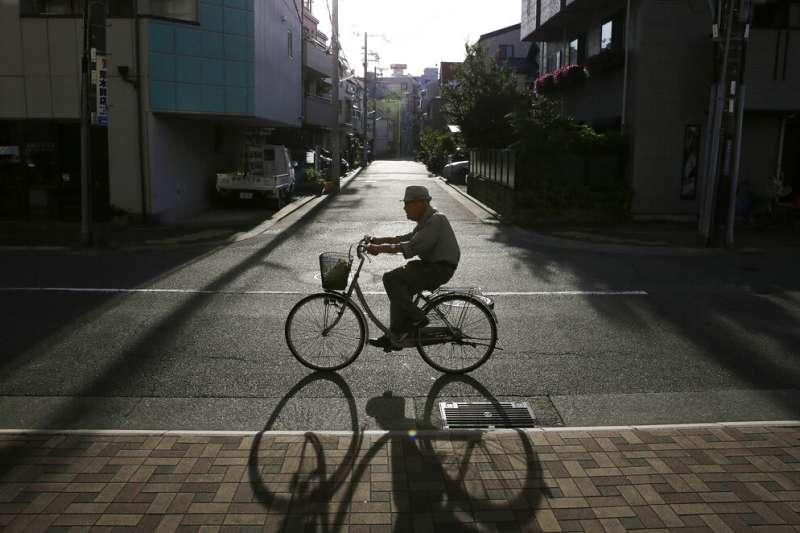 日本老人,日本神戶的一名老人在傍晚騎著腳踏車。(美聯社)