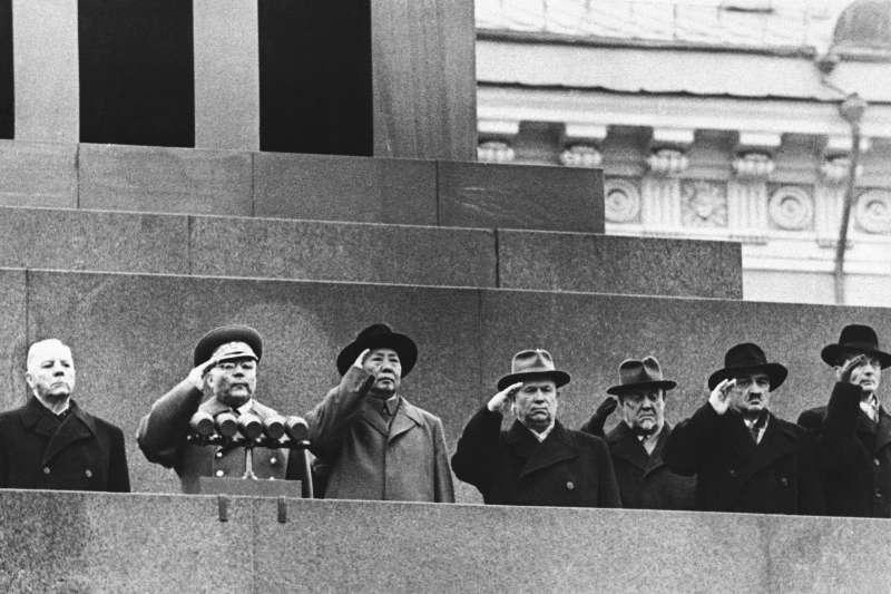中共的成立,蘇聯功不可沒。圖為1957年,毛澤東與一排蘇聯領導人站在列寧墓上向紅場遊行軍隊致。(資料照,AP)