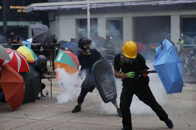 2019年9月29日,香港反送中,「全球連線、共抗極權」大遊行,示威者以雨傘抵擋警方催淚彈(AP)