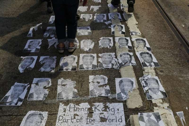 中共建政70周年10月1日這天,香港10萬「反送中」民眾上街示威,踩踏習近平肖像。(AP)