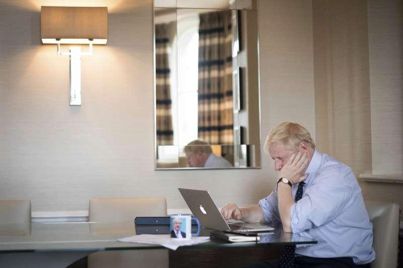 10月2日,英國首相強森正在準備脫歐協議最終版的會議簡報。(AP)