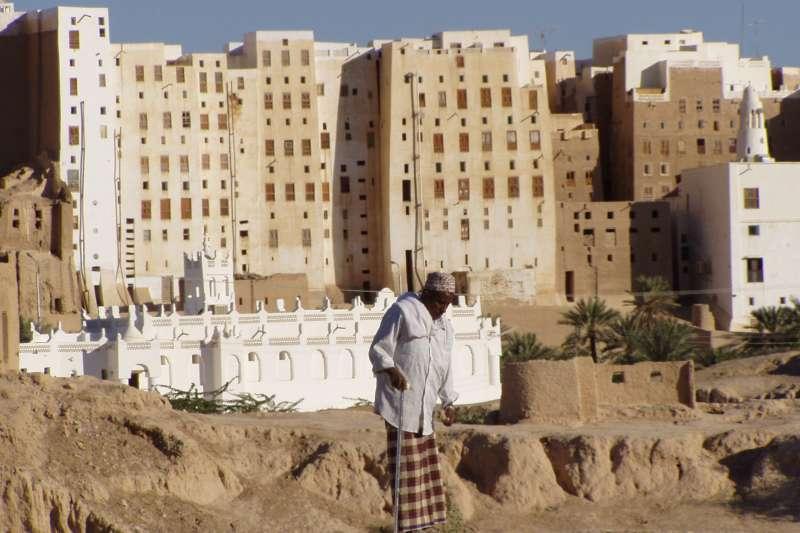一名老者站在示巴姆的泥造大樓群前,這些數百年古蹟因為葉門內戰而逐漸傾頹。(Dan@flickr_CCBYSA3.0)
